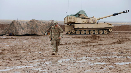 A U.S. soldier walks in front of a tank at an army base in Karamless town, east of Mosul, Iraq, December 25, 2016. Picture taken December 25, 2016. © Ammar Awad
