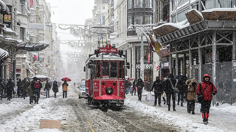 People walk on the Istiklal avenue during snowfalls in Istanbul on January 7, 2017. © 