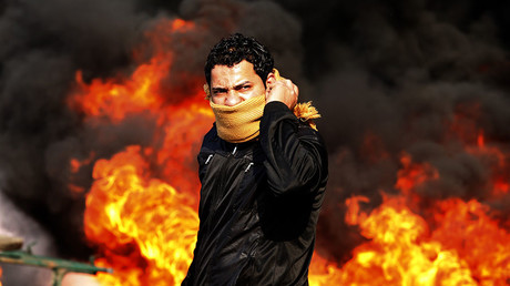 A protester stands in front of a burning barricade during a demonstration in Cairo January 28, 2011. © Goran Tomasevic