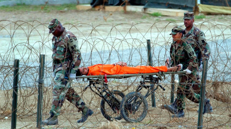 A detainee is carried by military police after being interrogated by