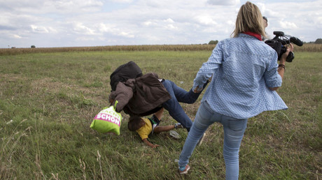 A migrant carrying a child falls after tripping on TV camerawoman (R) Petra Laszlo while trying to escape from a collection point in Roszke village, Hungary, September 8, 2015. © Marko Djurica / Reuters