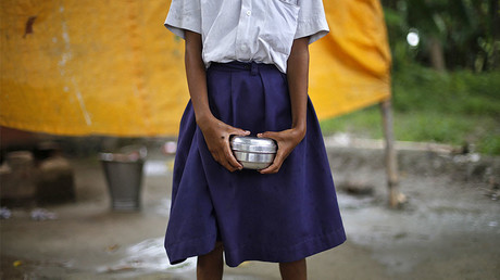 FILE PHOTO: A school girl holds a container to receive her free mid-day meal, at primary school, India. © Adnan Abidi