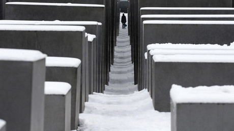 Person walks through snow covered Holocaust memorial in Berlin © Tobias Schwarz