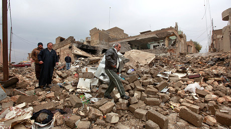 People walk on the wreckage of buildings destroyed by clashes in Qadisiyah neighborhood north of Mosul, Iraq © Alaa Al-Marjani