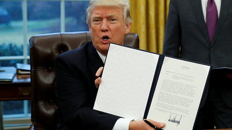 U.S. President Donald Trump holds up the executive order on withdrawal from the Trans Pacific Partnership after signing it in the Oval Office of the White House in Washington January 23, 2017. © Kevin Lamarque