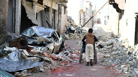 A boy pushes a wheelchair along a damaged street in the east Aleppo neighborhood of al-Mashatiyeh, Syria, January 4, 2017. © Bassam Diab / UNHCR