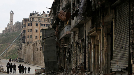 People walk past damaged shops in the Old City of Aleppo, Syria January 31, 2017. © Ali Hashisho