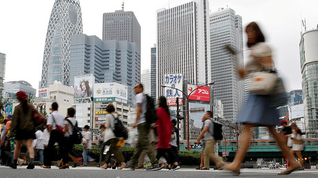 People cross a street in front of high-rise buildings in the Shinjuku district in Tokyo © Toru Hanai