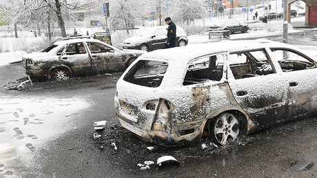 A policeman investigates a burnt car in the Rinkeby suburb outside Stockholm, Sweden February 21, 2017. © TT News Agency / Fredrik Sandberg / via REUTERS