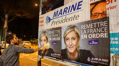 Member of the National Front youths puts up presidential campaign posters of Marine Le Pen © Robert Pratta
