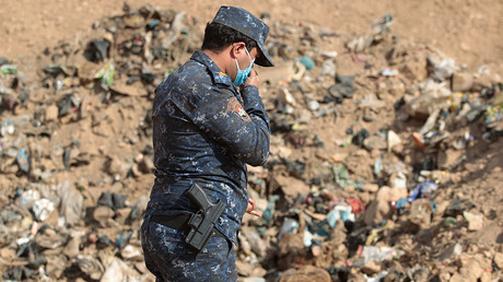 FILE PHOTO: A member of the Iraqi forces checks a mass grave in the Hamam al-Alil area on November 7, 2016  © Ahmad Al-Rubaye