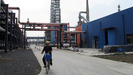 An employee rides a bike on a road near refinery plants of Chambroad Petrochemicals, in Boxing, Shandong Province, China. © Meng Meng