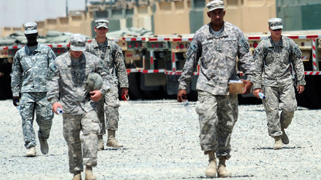 FILE PHOTO U.S. soldiers walk near vehicles at Camp Arifjan, Kuwait © Stephanie McGehee