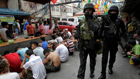 Members of the police SWAT team guard residents who were rounded up in Manila © Czar Dancel / Reuters