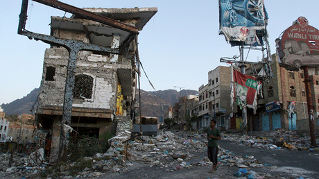 FILE PHOTO: A man walks past a destroyed building, in Yemen's southwestern city of Taiz. ©Anees Mahyoub