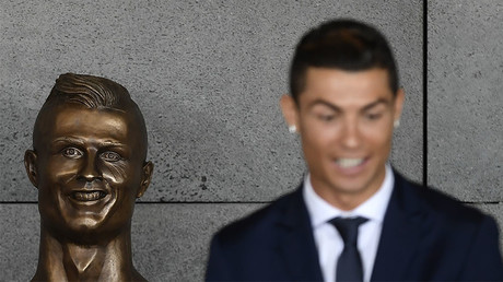 Portuguese footballer Cristiano Ronaldo stands beside a bust presented during a ceremony to rename Madeira's airport in Funchal as 'Cristiano Ronaldo', on Madeira island, on March 29, 2017. © 
