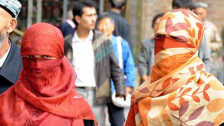 Uighur women wearing face veils walk on a street in Urumqi © Stringer