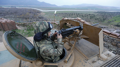 A Turkish soldier on an armoured military vehicle surveys the border line between Turkey and Syria. © Murad Sezer