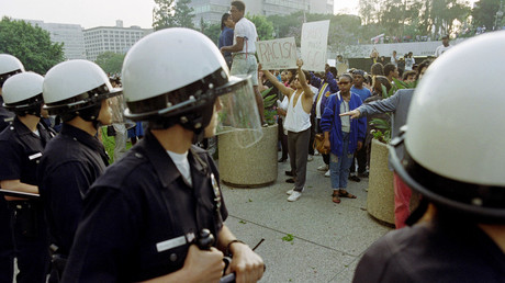 Police officers stand by as demonstrators gather April 29, 1992 at the Parker Center to protest after the acquittal of four LAPD officers accused of beating black motorist Rodney King in March 1991.