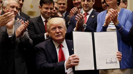US President Donald Trump displays an Executive Order on
