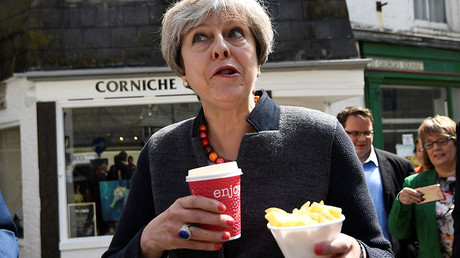 Britain's Prime Minister Theresa May enjoys some chips during a campaign stop in Mevagissey, Cornwall, May 2, 2017. © Dylan Martinez