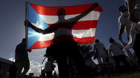 FILE PHOTO: A protester holding a Puerto Rico's flag © Alvin Baez