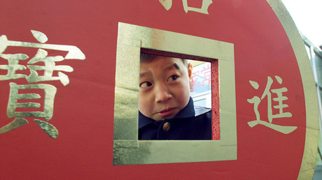 A boy looks through a giant coin in Beijing © Natalie Behring