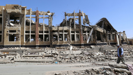 FILE PHOTO: A man walks past a building destroyed by Saudi-led air strikes, Yemen. © Naif Rahma