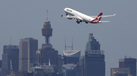 A Qantas Airways Airbus A330-300 jet takes off from Sydney International Airport over the city skyline © Jason Reed