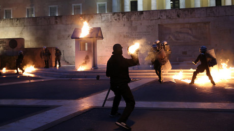 A masked demonstrator throws a petrol bomb to riot police outside the parliament building, Athens, Greece, May 18, 2017. © Costas Baltas