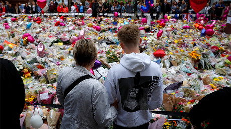 A boy wearing an Ariana Grande hoodie looks at flowers and tributes left for the victims of the attack on Manchester Arena, Britain. © Phil Noble