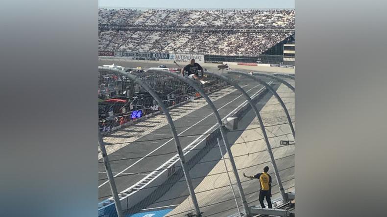 Crazed NASCAR fan climbs fence above speeding cars (VIDEO, PHOTOS)