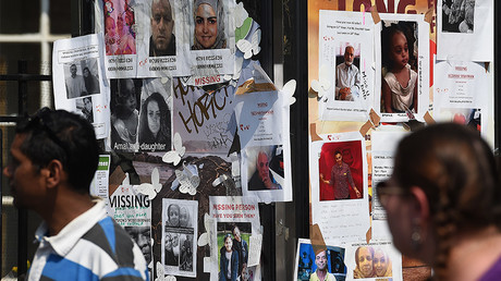 People pass posters showing images of missing people in Grenfell Tower block fire. © Paul Ellis
