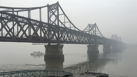 FILE PHOTO Trucks move across the bridge linking North Korea with the Chinese border city of Dandong © Megha Rajagopalan