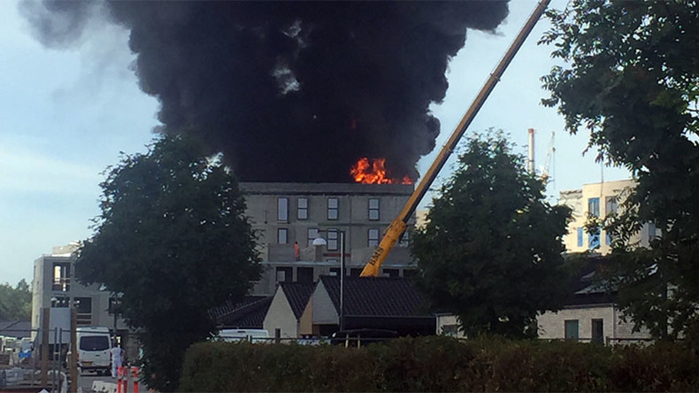 Man escapes burning building by holding on to crane hook (VIDEO)
