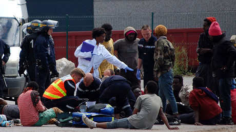 Police officers and emergency workers intervene as injured migrants lay on the ground after clashes in Calais, on July 1, 2017 © Bernard Barron