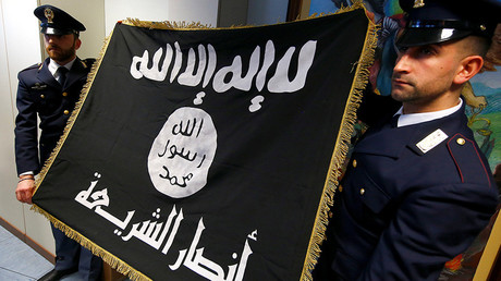 Police officers hold a black Islamic State flag that was seized in a raid. Rome, Italy, January 10, 2017 © Tony Gentile