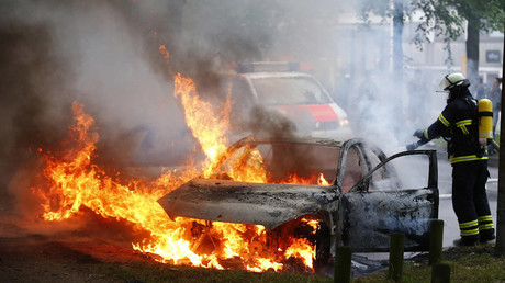 A firefighter works at the scene where a number of cars burnt down during the G20 summit in Hamburg, Germany, July 7, 2017. © Hannibal Hanschke