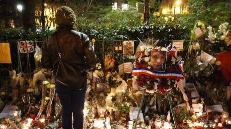 A woman looks at flowers, candles and messages in tribute to victims near the Bataclan concert hall in Paris, France, November 20, 2015. © Charles Platiau