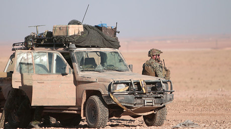 FILE PHOTO: A U.S. fighter stands near a military vehicle, north of Raqqa city, Syria. © Rodi Said