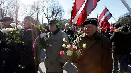 FILE PHOTO: Men holding flowers take part in the annual procession commemorating the Latvian Waffen-SS (Schutzstaffel) unit, also known as the Legionnaires, in Riga © Ints Kalnins