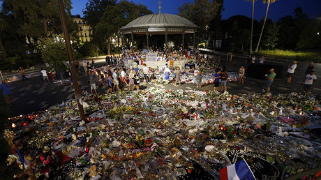 People walk next to floral tributes, notes and candles placed in the road for victims of the deadly Bastille Day attack, on July 20, 2016 in Nice, southern France © Valery Hache © AFP