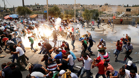 Palestinians react following tear gas that was shot by Israeli forces after Friday prayer on a street outside Jerusalem's Old city July 21, 2017. © Ammar Awad