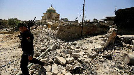 A member of the Iraqi Counter Terrorism Service (CTS) walks past the ruined Grand al-Nuri Mosque in the Old City of Mosul, Iraq © Thaier Al-Sudani