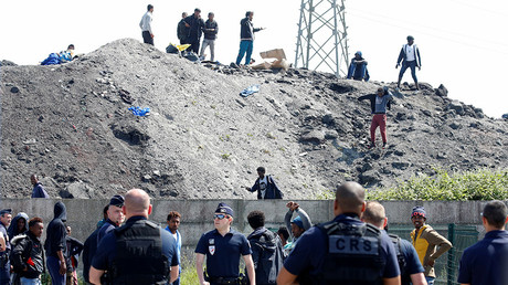 French riot police and migrants are seen as French authorities block their access to a food distribution point in Calais, France, June 1, 2017 © Pascal Rossignol