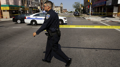 A police officer attempts to secure a crime scene in West Baltimore, Maryland © Jim Bourg