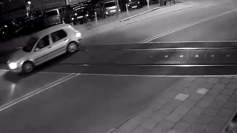 Car misses train by seconds after crashing through crossing barrier (VIDEO)