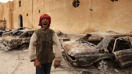 FILE PHOTO: A man gestures in front of burnt vehicles in a state security building in Tobruk, east of Libya February 24, 2011. © Suhaib Salem