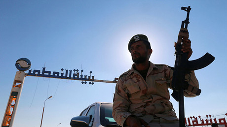 Member of Libyan forces loyal to eastern commander Khalifa Haftar holds a weapon as he sits on a car in front of the gate at Zueitina oil terminal in Zueitina, west of Benghazi. © Reuters