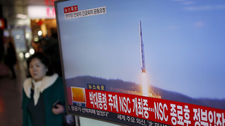 FILE PHOTO A passenger walks past a TV screen broadcasting a news report on North Korea's long range rocket launch © Kim Hong-Ji
